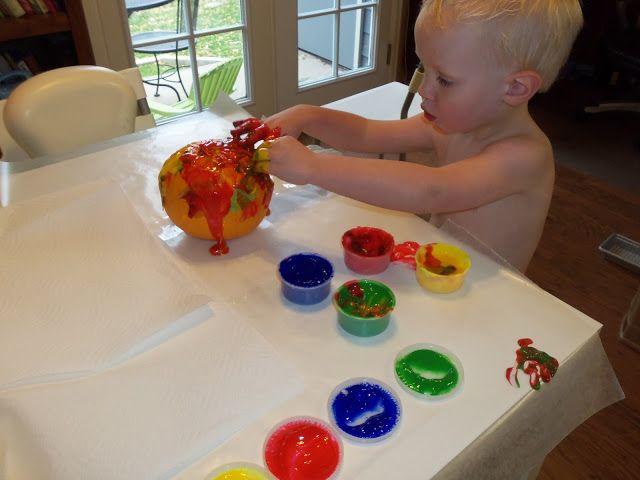 kid fingerpainting a pumpkin