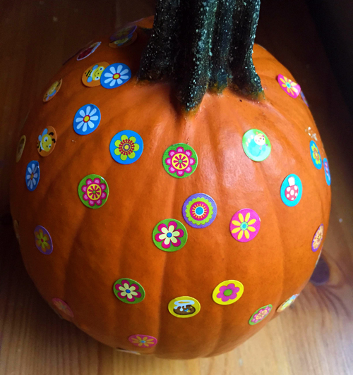sticking stickers to a pumpkin